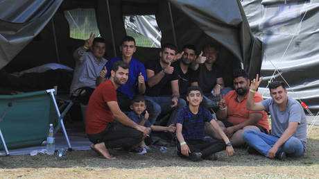 Migrants react to the camera as they sit by a tent in a camp near the border town of Kapciamiestis, Lithuania