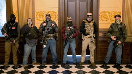 FILE PHOTO: Militia members accused of conspiring to kidnap Michigan Governor Gretchen Whitmer stand in front of the governor's office after a protest at the state capitol building, in Lansing, Michigan, April 30, 2020.