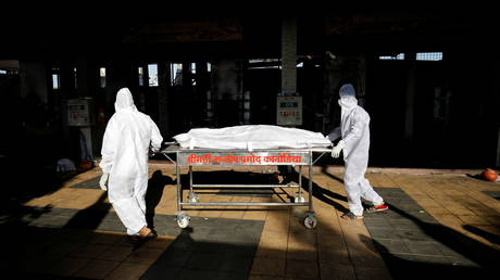 FILE PHOTO. Workers move the body of a person who died from the coronavirus disease inside the Kurukshetra crematorium in Surat, India.