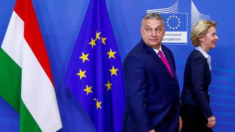 Hungarian Prime Minister Viktor Orban walks with European Commission President Ursula von der Leyen