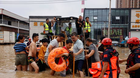 Rescue workers operate a front loader to evacuate residents on a flooded road following heavy rainfall in Zhengzhou, Henan province, China July 22, 2021. © REUTERS/Aly Song