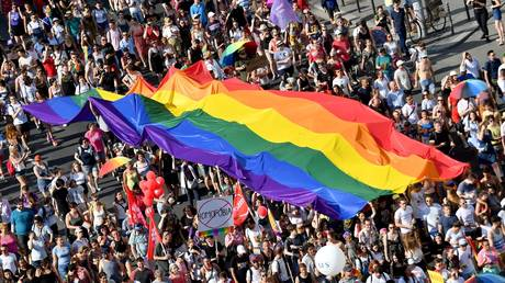 In this file photo taken on July 06, 2019 people march with their giant rainbow flag during the lesbian, gay, bisexual and transgender (LGBT) Pride Parade from the parliament building in downtown Budapest. © ATTILA KISBENEDEK / AFP