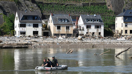 Police officers float on a boat on the river Ahr as damaged houses reflect onto the water and wyneyards are seen on the hills in the background, in Mayschoss, Rhineland-Palatinate, western Germany, on July 21, 2021, after devastating floods hit the region. © CHRISTOF STACHE / AFP