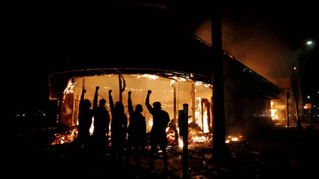 FILE PHOTO: Rioters are shown outside a burning Minneapolis liquor store in May 2020.