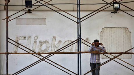 A worker talks on a phone as he stands in front of a wall with removed Flipkart logo in Bengaluru, India.