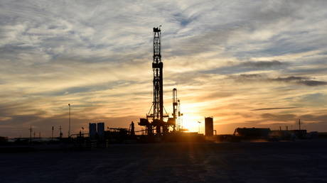 FILE PHOTO: Drilling rigs operate at sunset in Midland, Texas, US