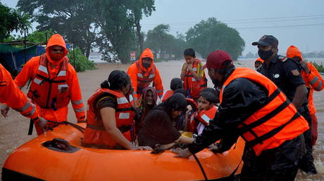 Rescue workers evacuate people from a flooded area to safer places after heavy rains in Kolhapur in the western state of Maharashtra, India, July 23, 2021. © REUTERS/Abhijeet Gurjar
