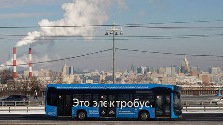"""An electric bus travels along a road in Moscow, Russia. The sign on the bus reads: """"It's an electric bus""""."""