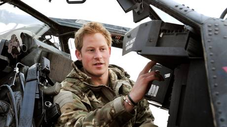 FILE PHOTO. Britain's Prince Harry (R) makes his early morning pre-flight checks at the British controlled flight-line at Camp Bastion in Afghanistan's Helmand Province. © AFP / JOHN STILLWELL