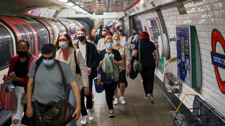 FILE PHOTO: People, some wearing protective face masks, walk along a platform at Oxford Circus underground station, amid the coronavirus disease (COVID-19) pandemic, in London, Britain, July 4, 2021.© Reuters / Henry Nicholls