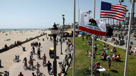 People sit at the beach in Huntington Beach, California, US, May 23, 2020.