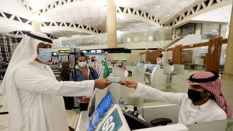 A Saudi man wearing a face mask gets his passport from a Saudi Immigration officer, at the King Khalid International Airport, in Riyadh, Saudi Arabia (FILE PHOTO) © REUTERS/Ahmed Yosri