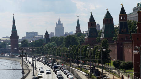 Vehicles drive along an embankment of the Moskva river near the Kremlin walls in central Moscow, Russia, July 1, 2016.