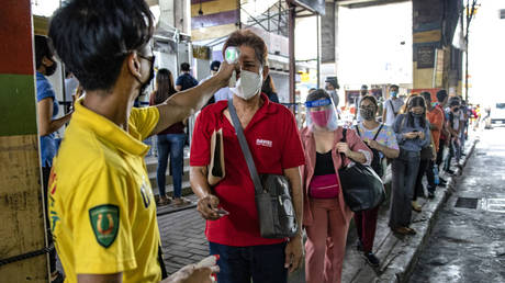 A commuter's temperature is checked by a worker before being allowed to board a bus on the first day of relaxed quarantine measures on June 1, 2020 in Caloocan, Metro Manila, Philippines. © Ezra Acayan/Getty Images