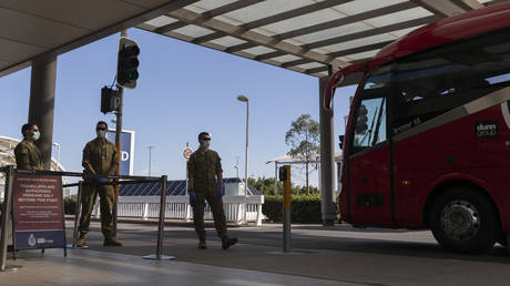 Army personnel watch as a charter bus that unloaded crew from the Ruby Princess Cruise ship departs Sydney Airport on April 23, 2020 in Sydney, Australia. © Brook Mitchell/Getty Images