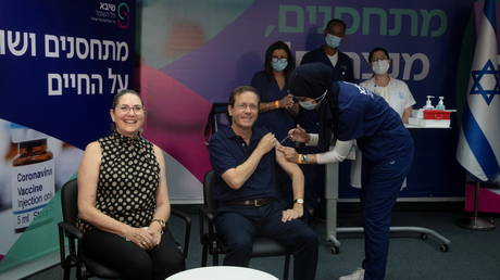 Israeli President Isaac Herzog receives a third dose of coronavirus disease (COVID-19) vaccine while his wife, Michal, reacts, at Sheba Medical Center in Ramat Gan, Israel, July 30, 2021. © Maya Alleruzzo/Pool via REUTERS