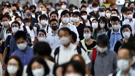 FILE PHOTO: Commuters wearing protective masks amid the coronavirus disease (COVID-19) outbreak make their way at Shinagawa station in Tokyo, Japan, July 28, 2021. © REUTERS/Kim Kyung-Hoon