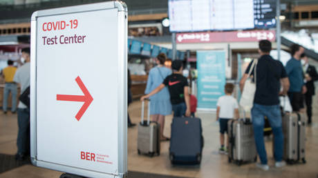 """Passengers stand with suitcases at the BER """"Willy Brandt"""" airport in Brandenburg, near Schoenefeld and Berlin, on July 28, 2021."""