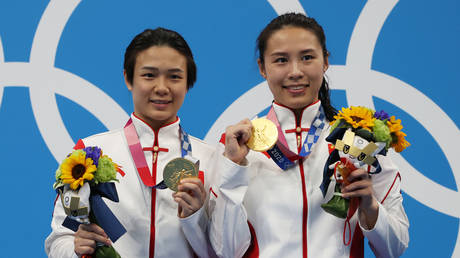Tingmao Shi and Han Wang of Team China pose with the gold medals on the podium during the medal ceremony for the Women's 3m Springboard Finals on day two of the Tokyo 2020 Olympic Games at Tokyo Aquatics Centre on July 25, 2021 in Tokyo, Japan. © Al Bello/Getty Images