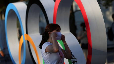 A woman adjusts her protective mask next to an Olympic rings monument outside the National Stadium, the main stadium of Tokyo 2020 Olympics. © Reuters / Issei Kato