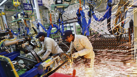 Employees work on the assembly line inside the automobile manufacturing plant in Tapukara, India