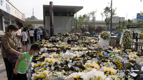 People stand next to flowers placed at an entrance to a subway station of Metro Line 5 in memory of flood victims following heavy rainfall in Zhengzhou, Henan province, China (FILE PHOTO) © China Daily via REUTERS