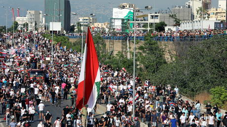 People carry flags and banners as they march to mark the one-year anniversary of Beirut's port blast, in Beirut Lebanon on August 4, 2021.
