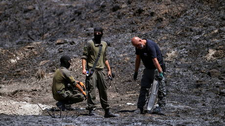 An Israeli bombs expert, accompanied by two soldiers, inspects the remains of a rocket that was fired at Israel from Lebanon, in Kiryat Shmona, Israel August 4, 2021 © REUTERS/Gil Eliyahu