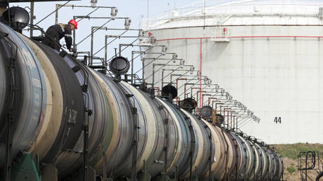 A worker controls the freight level of a tanker wagon at the Rosneft oil terminal in Arkhangelsk, Russia, May 30, 2007.