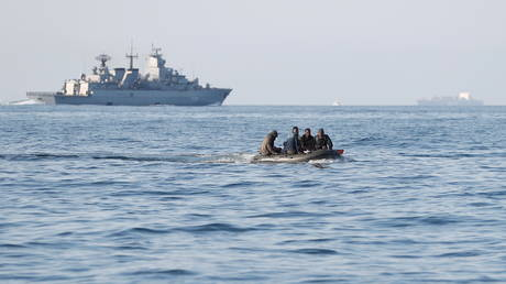 Migrants claiming to be from Darfur, Sudan cross the English Channel in an inflatable boat as a German warship passes by, near Dover, Britain, (FILE PHOTO) © REUTERS/Peter Nicholls