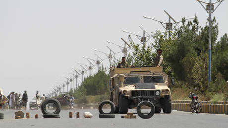FILE PHOTO. Afghan security personnel patrol along a road on the outskirts of Herat, on August 6, 2021.