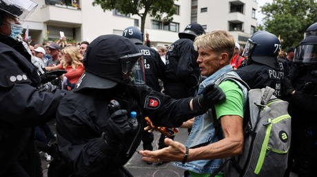 FILE PHOTO: Police officers scuffle with a demonstrator during a protest in Berlin, Germany, on August 1, 2021.