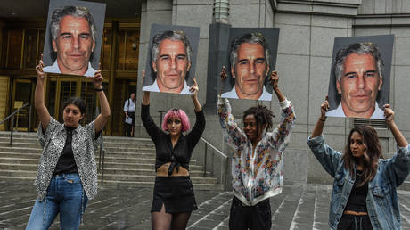 A protest group called 'Hot Mess' hold up signs of Jeffrey Epstein in front of the Metropolitan Correction Center on July 8, 2019 in New York City.