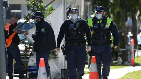 Police officers patrol the streets of Campbelltown, a suburb of Sydney, Australia, August 4, 2021. © Saeed Khan/AFP