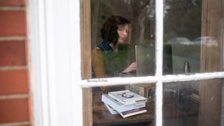 FILE PHOTO. University of Hull lecturer in Film and Media and historian of British cinema, Dr Laura Mayne prepares a remote learning session for her students from her home in Hull, northern England.© AFP / OLI SCARFF