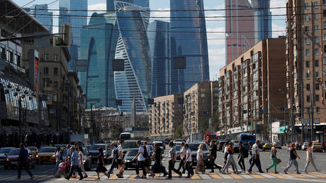 Pedestrians cross the road near the Moscow International Business Center in Moscow, Russia, August 10, 2018.