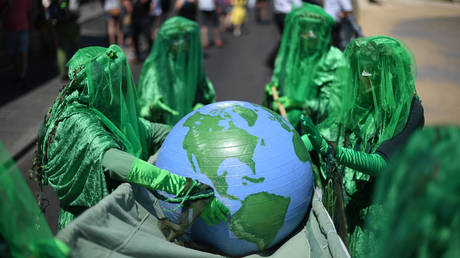 FILE PHOTO. Extinction Rebellion environmental activists do a performance as they protest in the streets of St Ives, Cornwall during the G7 summit on June 13, 2021. © AFP / DANIEL LEAL-OLIVAS