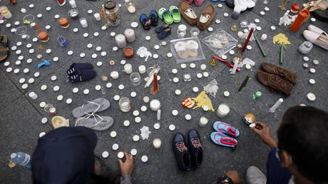 """FILE PHOTO. People lay flowers, candles, and shoes at an impromptu vigil as part of """"No Pride in Genocide"""" rally in Toronto, Ontario, Canada, July 1, 2021. © AFP / Cole Burston"""