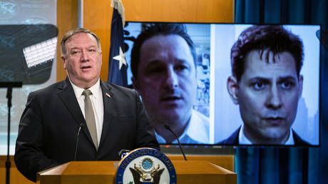 FILE PHOTO. Michael Spavor, a Canadian businessman and Michael Kovrig, right, a former Canadian diplomat are shown on a video monitor as US Secretary of State Mike Pompeo, speaks during a news conference at the State Department in Washington.© AFP / Manuel Balce CENATA