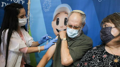 A man is shown receiving his third Covid-19 vaccine shot on Wednesday in Israel, where more than 715,000 people over age 60 have already been given such booster jabs.