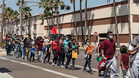 Migrants dropped off in McAllen, Texas, are shown earlier this year walking to a temporary shelter after being tested for Covid-19.