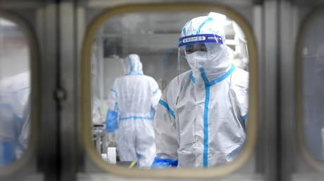 Medical workers in protective suits test nucleic acid samples following new cases of the coronavirus in Wuhan. © Reuters / China Daily