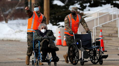 FILE PHOTO: Army National Guard troops wheel an elderly resident as she arrives at a mass vaccination site in White Plains, New York.