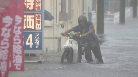 A man pushes a motorbike in a road flooded by heavy rain in Kurume, Fukuoka prefecture, western Japan, August 14, 202 © REUTERS /Kyodo