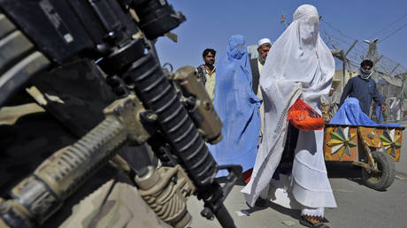 A US soldier stands guard in a street during a mission as Afghan women walk by, in Turkham Nangarhar, on October 2, 2011.