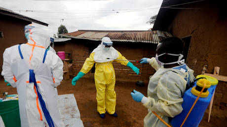 FILE PHOTO: A healthcare worker, who volunteered in the Ebola response, decontaminates his colleague in the eastern Congolese town of Beni in the Democratic Republic of Congo, October 8, 2019 © REUTERS/Zohra Bensemra
