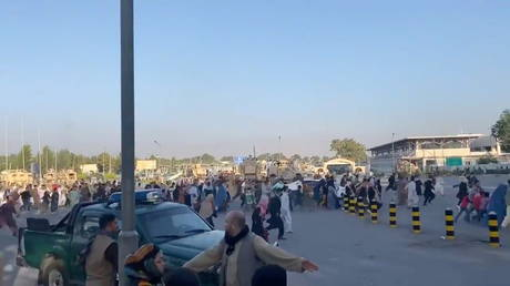 A horde of people run towards the Kabul Airport Terminal on August 16, 2021, in this still image taken from video obtained from social media.