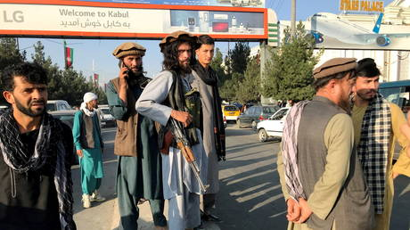 FILE PHOTO. A member of Taliban (C) stands outside Hamid Karzai International Airport in Kabul. ©REUTERS/Stringer