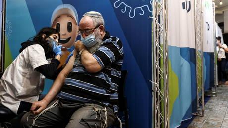 A elderly man receives his third dose of the coronavirus vaccine in Jerusalem. © Reuters / Ronen Zvulun