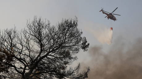 FILE PHOTO: A fire-fighting helicopter makes a water drop as a wildfre burns Athens. © Reuters / Costas Baltas